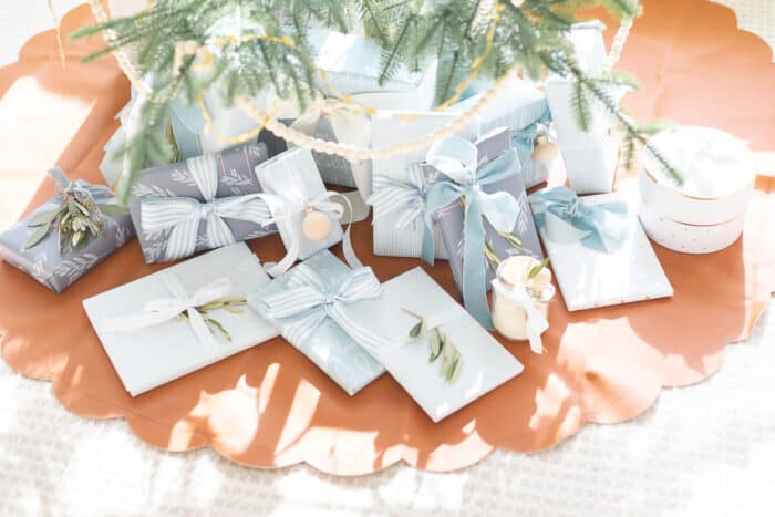 Blue and white gifts wrapped underneath a Scandinavian tree.