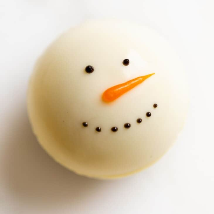 A snowman hot chocolate bomb on a white plate.