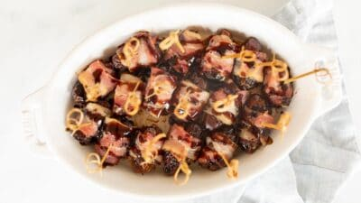 A white oval baking dish filled with dates wrapped in bacon, toothpicks in each one.