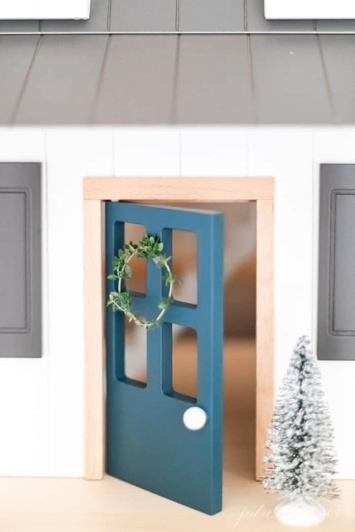 A child's doll house with a thyme wreath on the blue front door.
