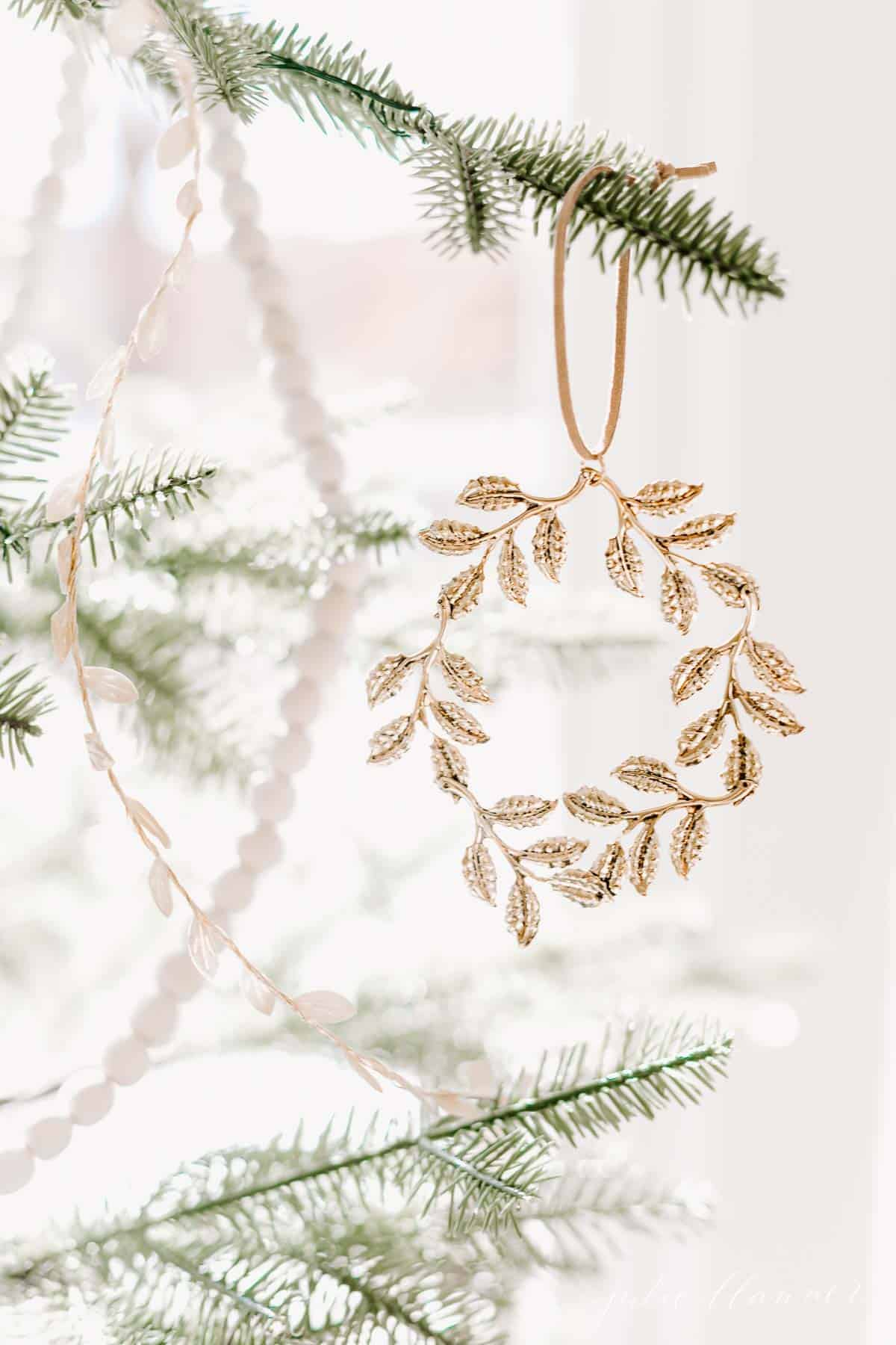 A close up of a gold wreath ornament on a Scandinavian Christmas tree.