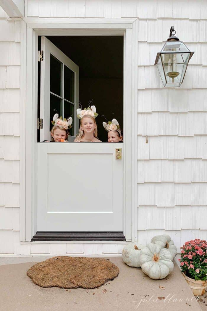 A white dutch door on the exterior of a white cottage, with a brass door knob, three little girls peeking over the bottom half of door.