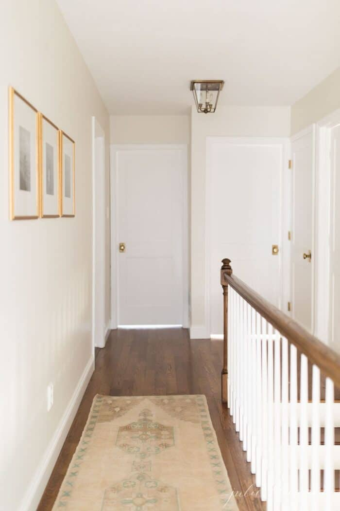 A long hallway in a home, painted white, with brass doorknobs on each wooden door.