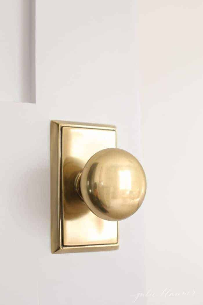 A white wooden door with a classic antique brass door knob.