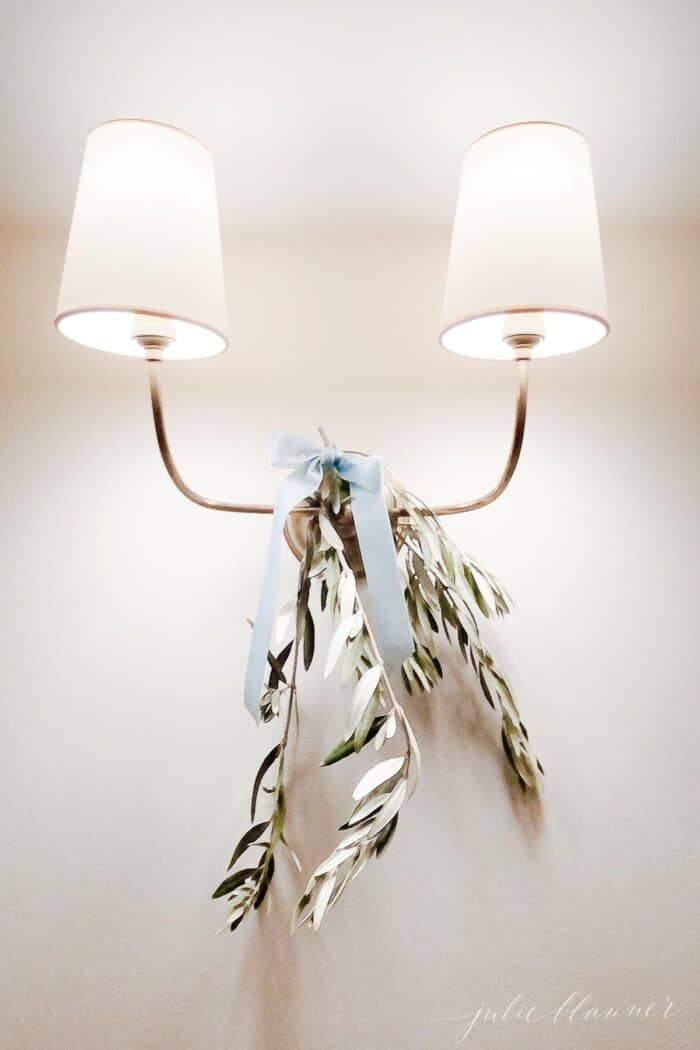 A gold sconce decorated with holiday greens and a blue velvet bow.
