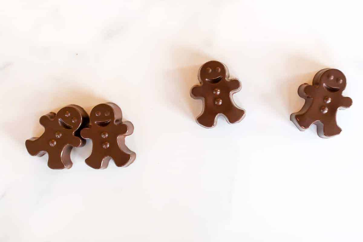 A group of dark chocolate hot chocolate bombs shaped as gingerbread men on a white marble surface.