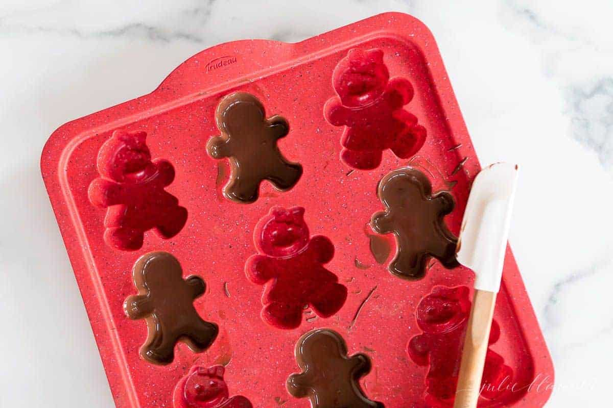 A red gingerbread man mold filled with dark chocolate.