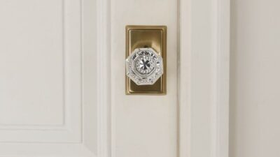 A white wooden door with a classic brass and crystal door knob.