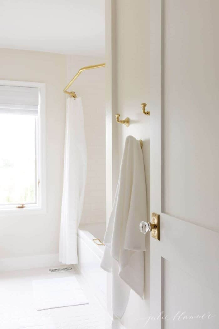 Looking into a white bathroom, with a wooden door featuring a brass and glass door knob.