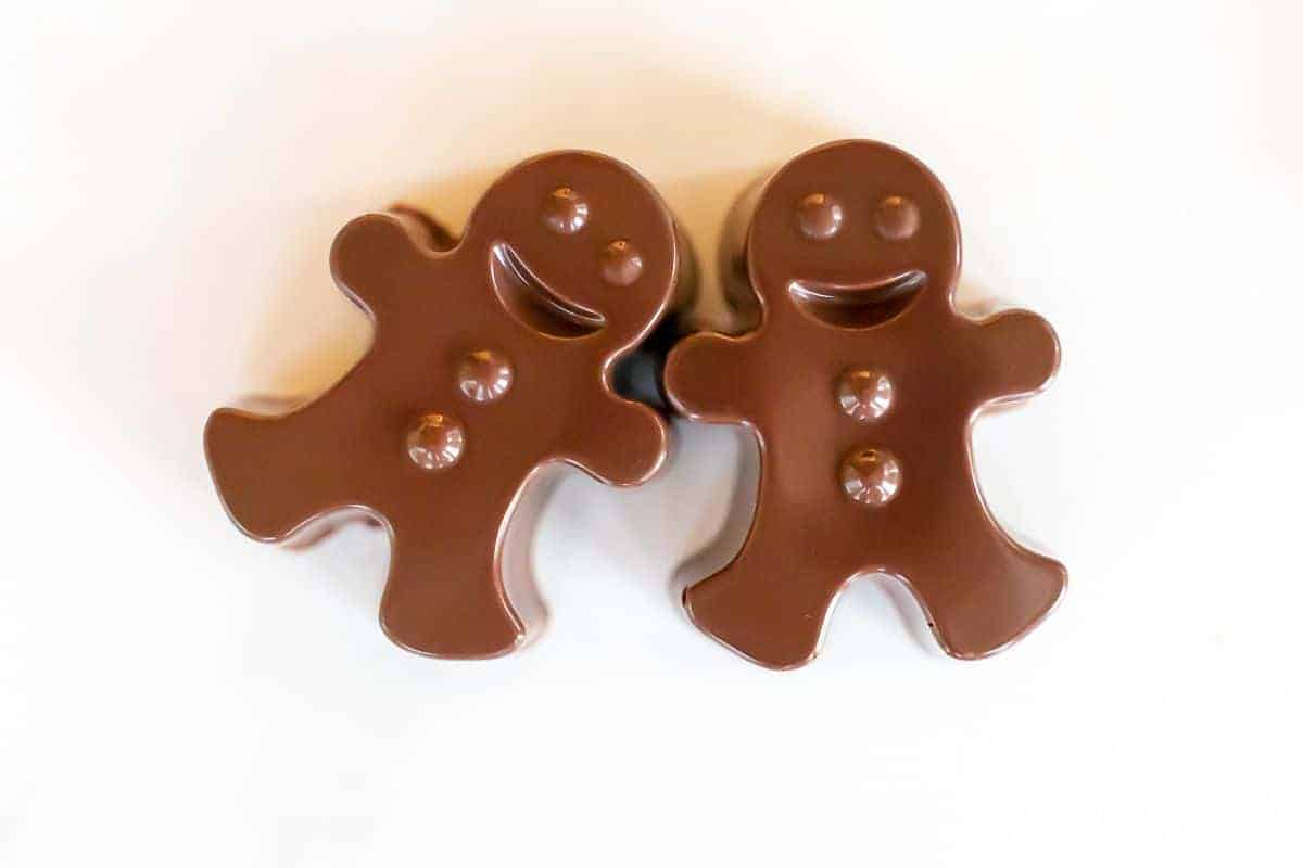 A pair of dark chocolate hot chocolate bombs shaped as gingerbread men on a white marble surface.