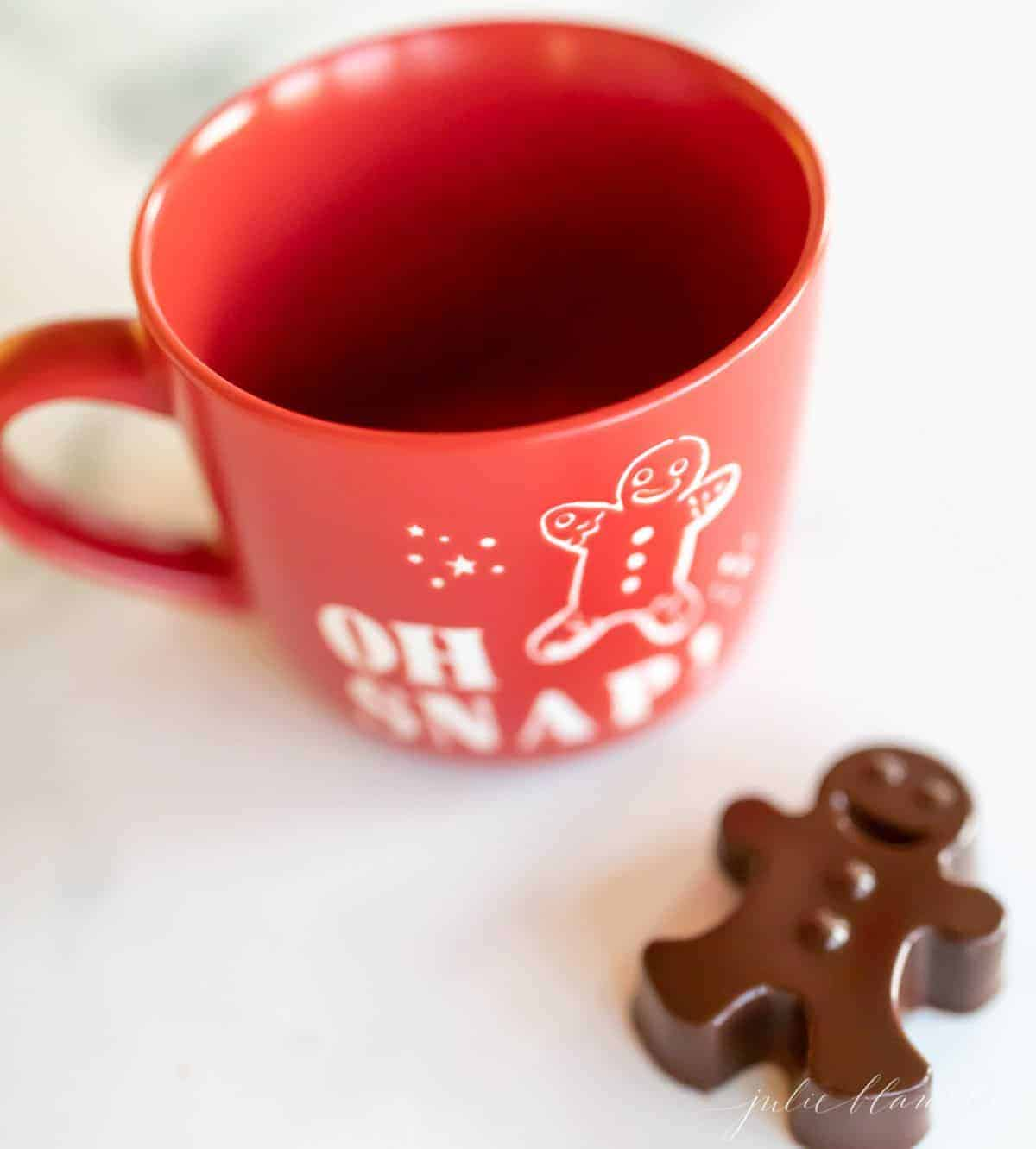 A red mug for hot chocolate, with a dark hot chocolate bomb shaped as a gingerbread man to the side.