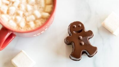 A red mug full of dark hot chocolate with marshmallows, with a dark chocolate gingerbread man to the side.