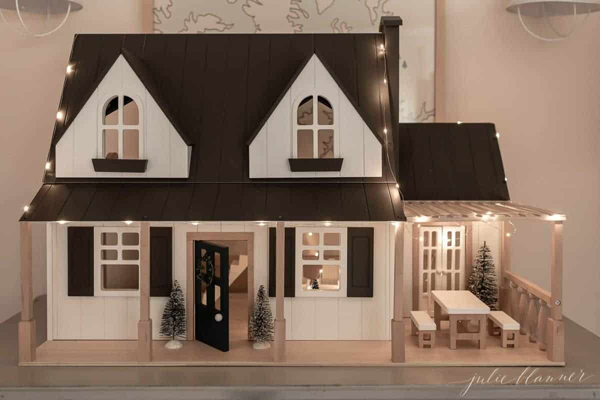 An up close look at a farmhouse dollhouse decorated with indoor Christmas lights ideas.