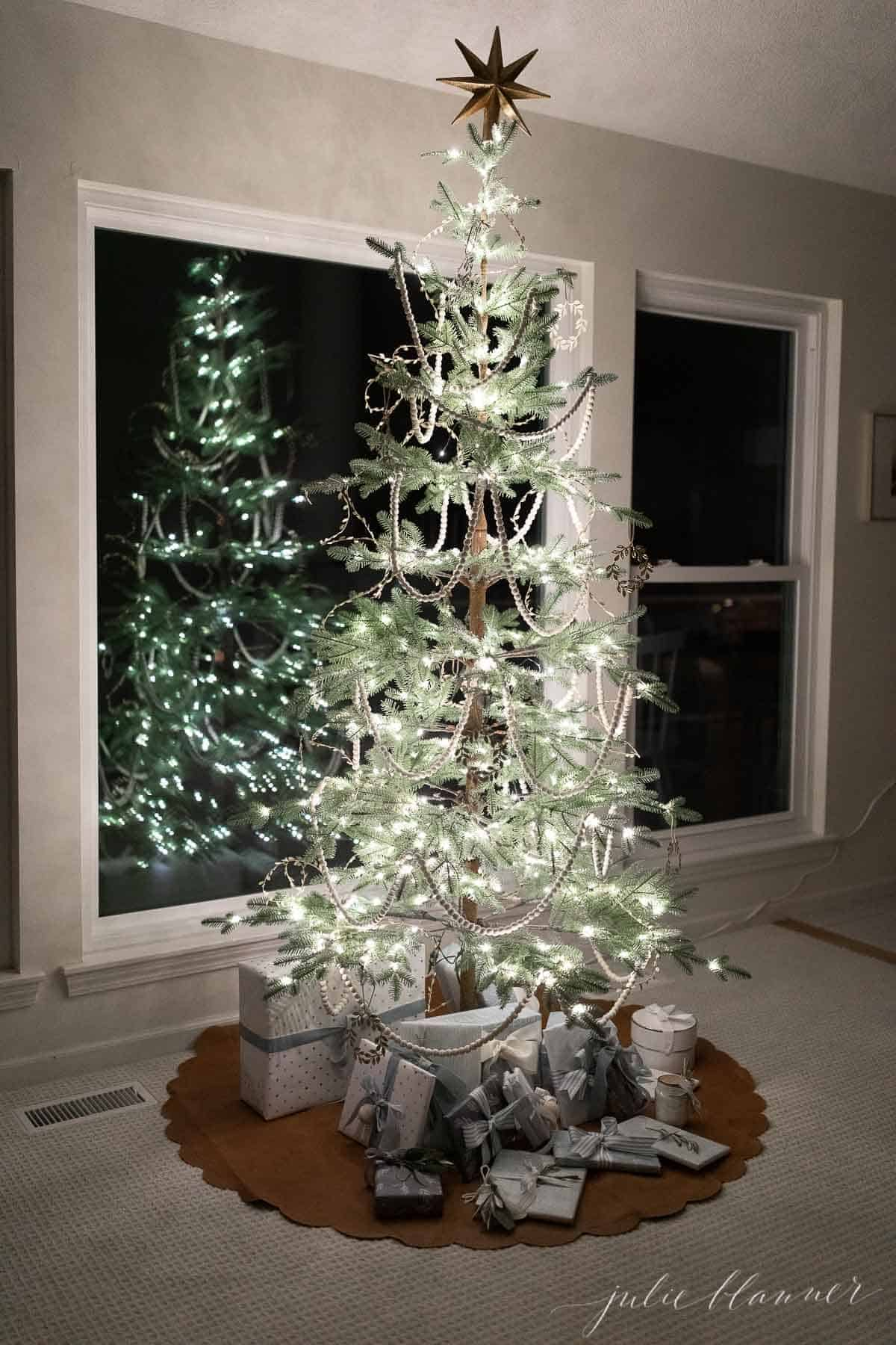 A sparsely decorated Scandinavian inspired Christmas tree reflecting in a window.