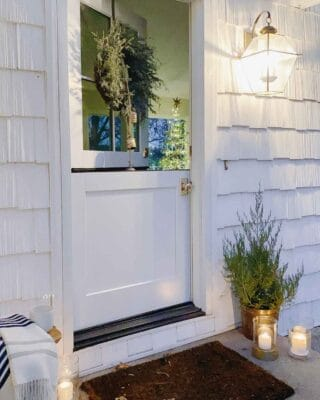 A dutch door on a white cottage decorated with candles and a mini cedar tree for Christmas.
