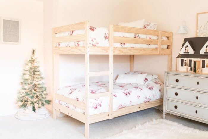 A wooden bunk bedroom with a small Christmas tree in the corner.