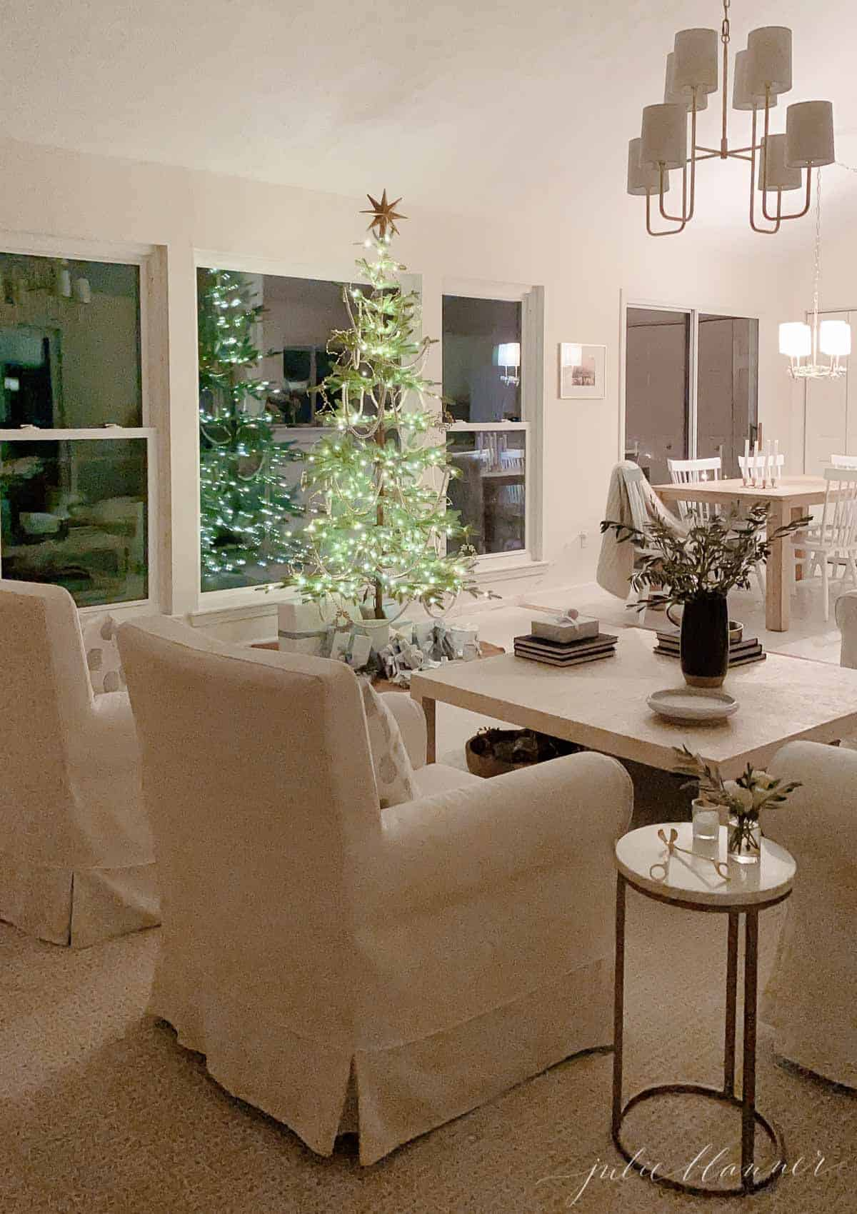 A white living room with a sparsely decorated Scandinavian Christmas tree.