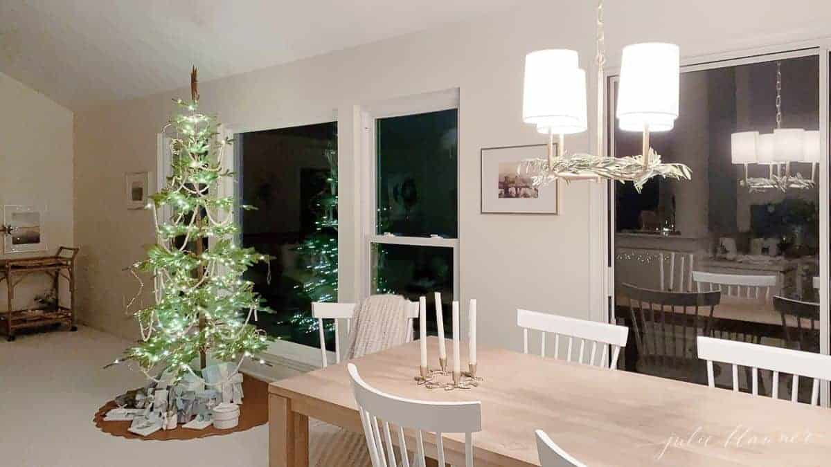 Looking past a kitchen dining room with a sparsely decorated Scandinavian Christmas tree.