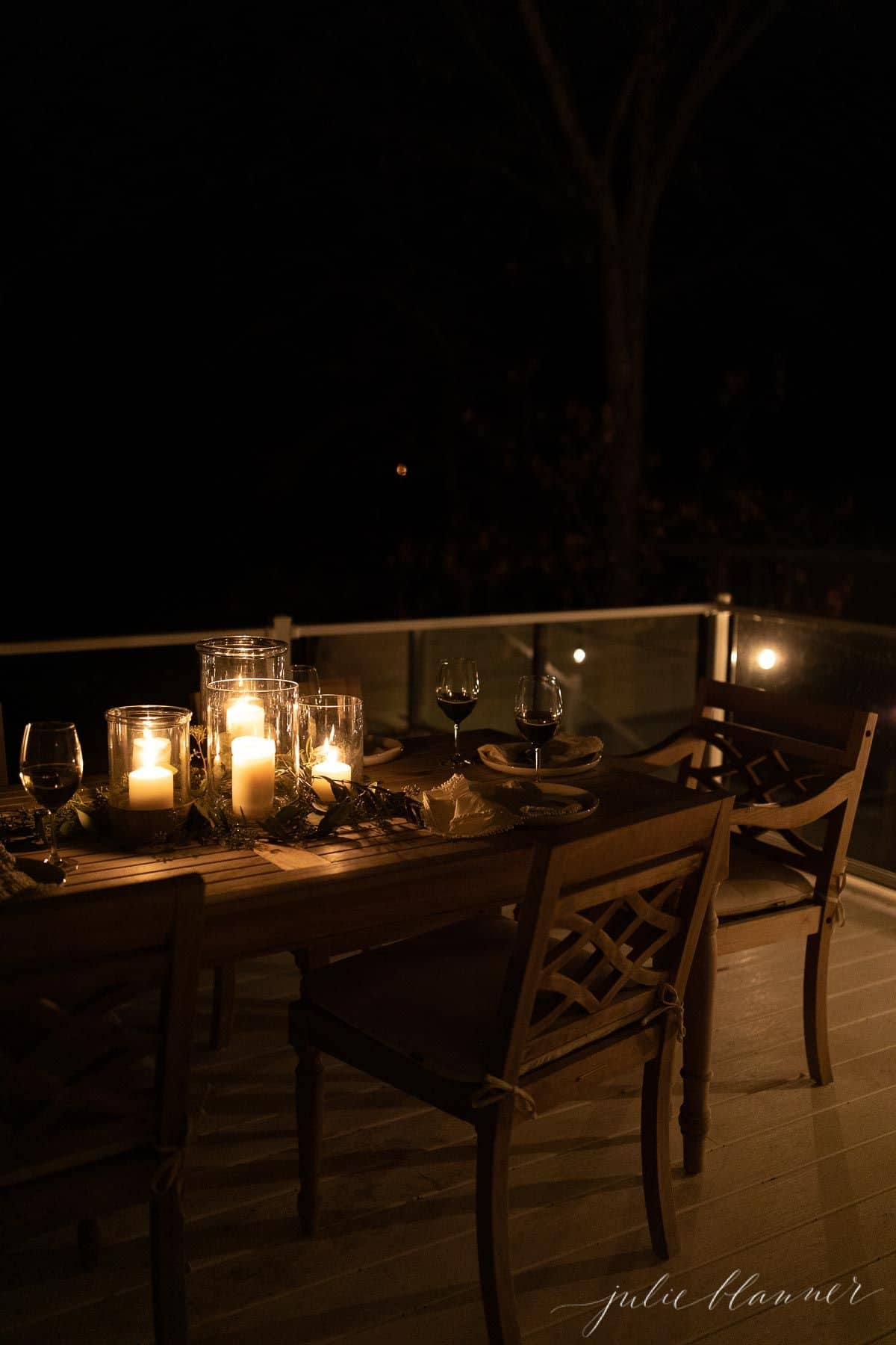 An outdoor dining table with a glowing candle centerpiece for Christmas.