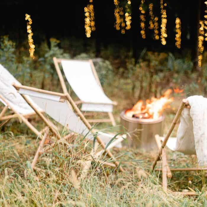 A roaring fire in a solo stove with twinkling outdoor Christmas lights for the holidays.