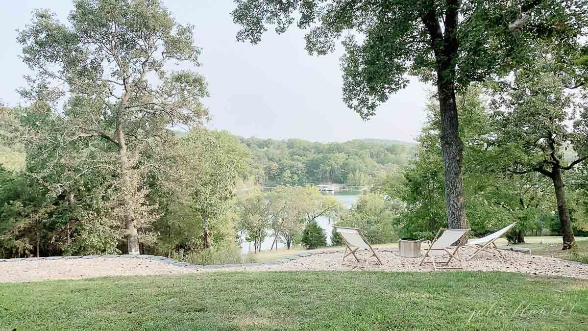 a lake view through trees, with a solo stove and wooden sling chairs surrounding.