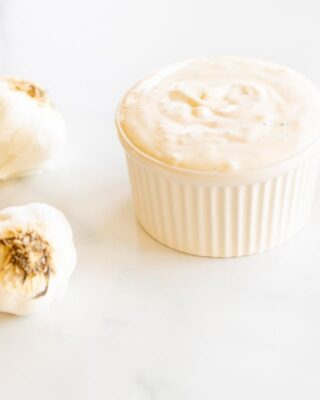 On a marble surface, a white ramekin dish full of fresh aioli, with heads of garlic to the side.