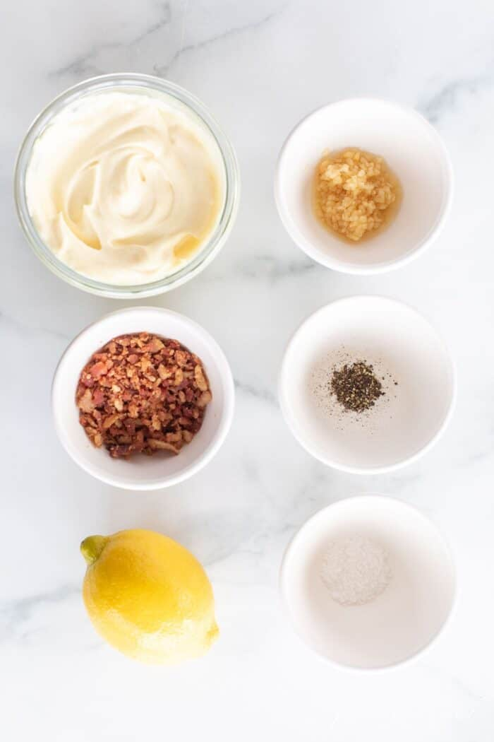 Small white bowls of ingredients for a bacon aioli recipe laid out on a marble surface.