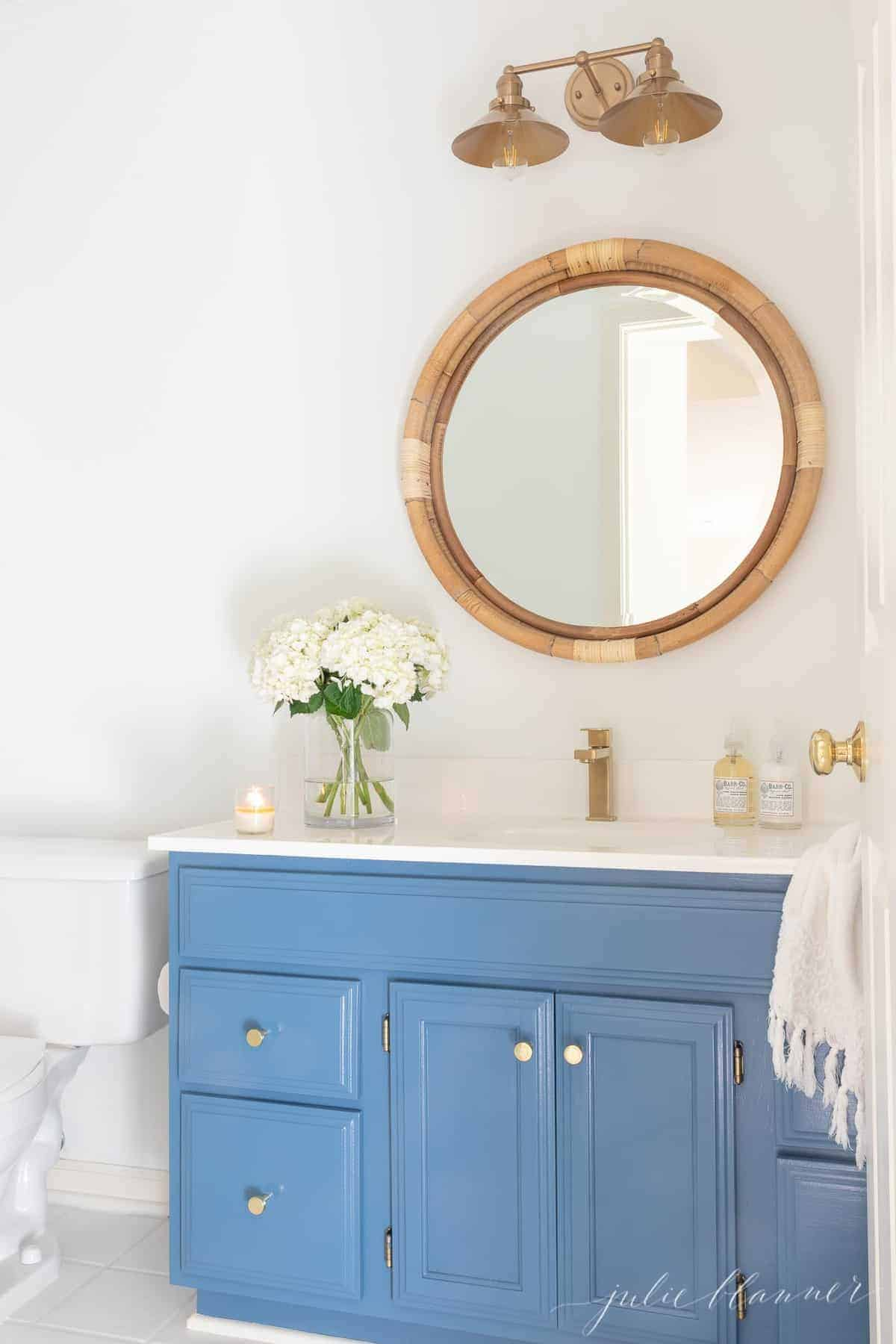A nautical style bathroom with a blue vanity, gold cabinet door knobs.