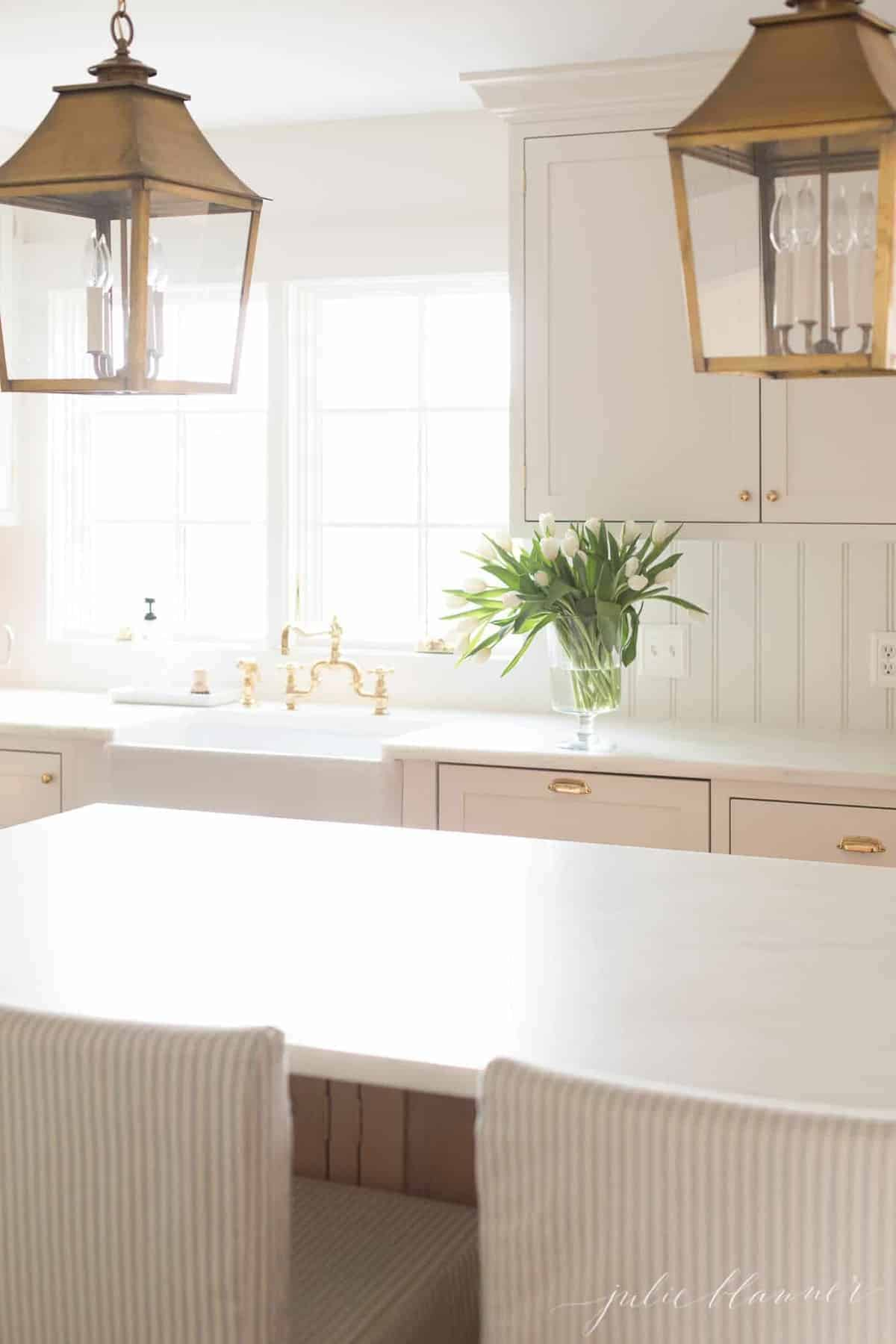 A white kitchen with shaker style cabinets, brass lanterns hanging over island.
