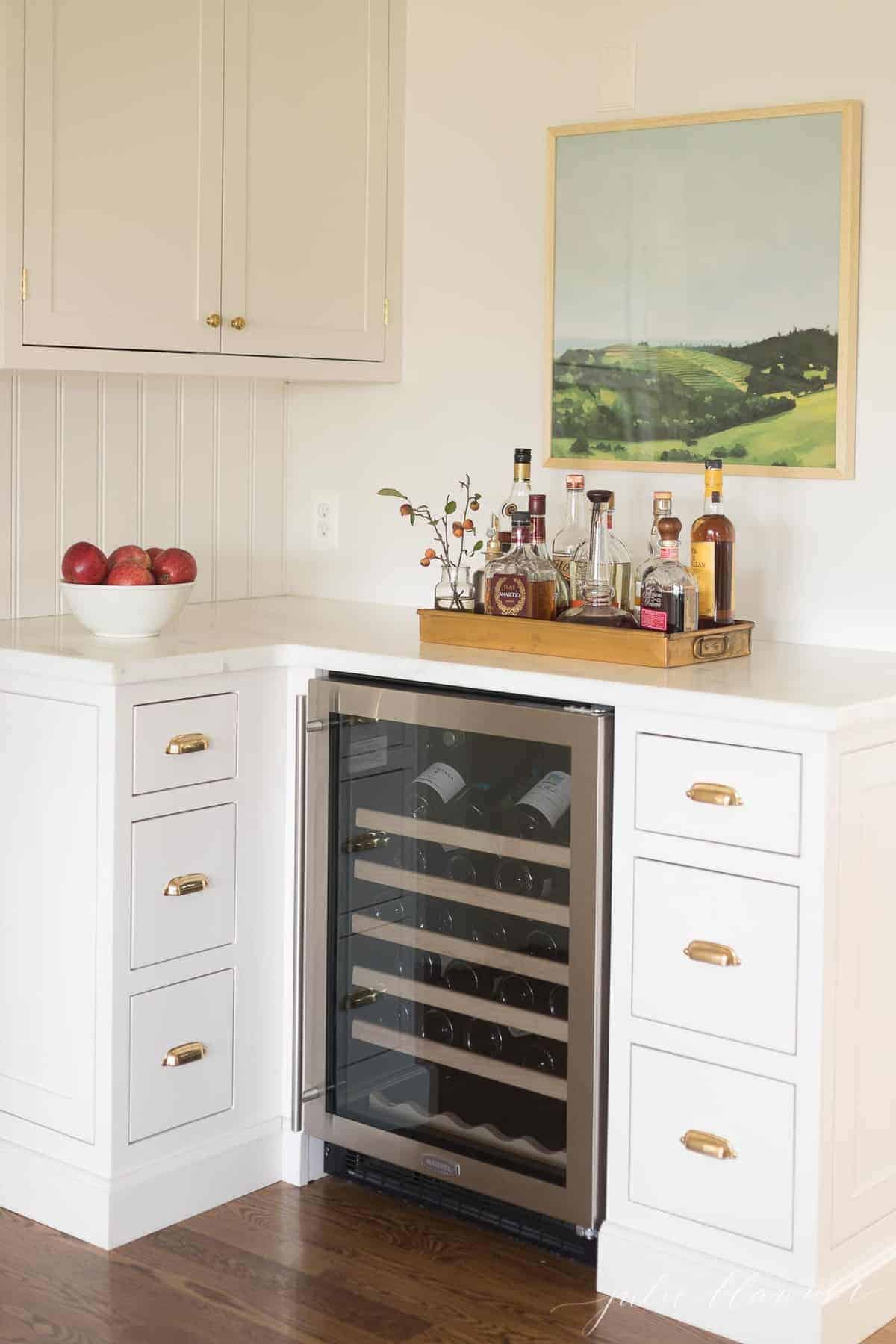 A wine bar area of a white kitchen with brass cup pulls on the drawers.