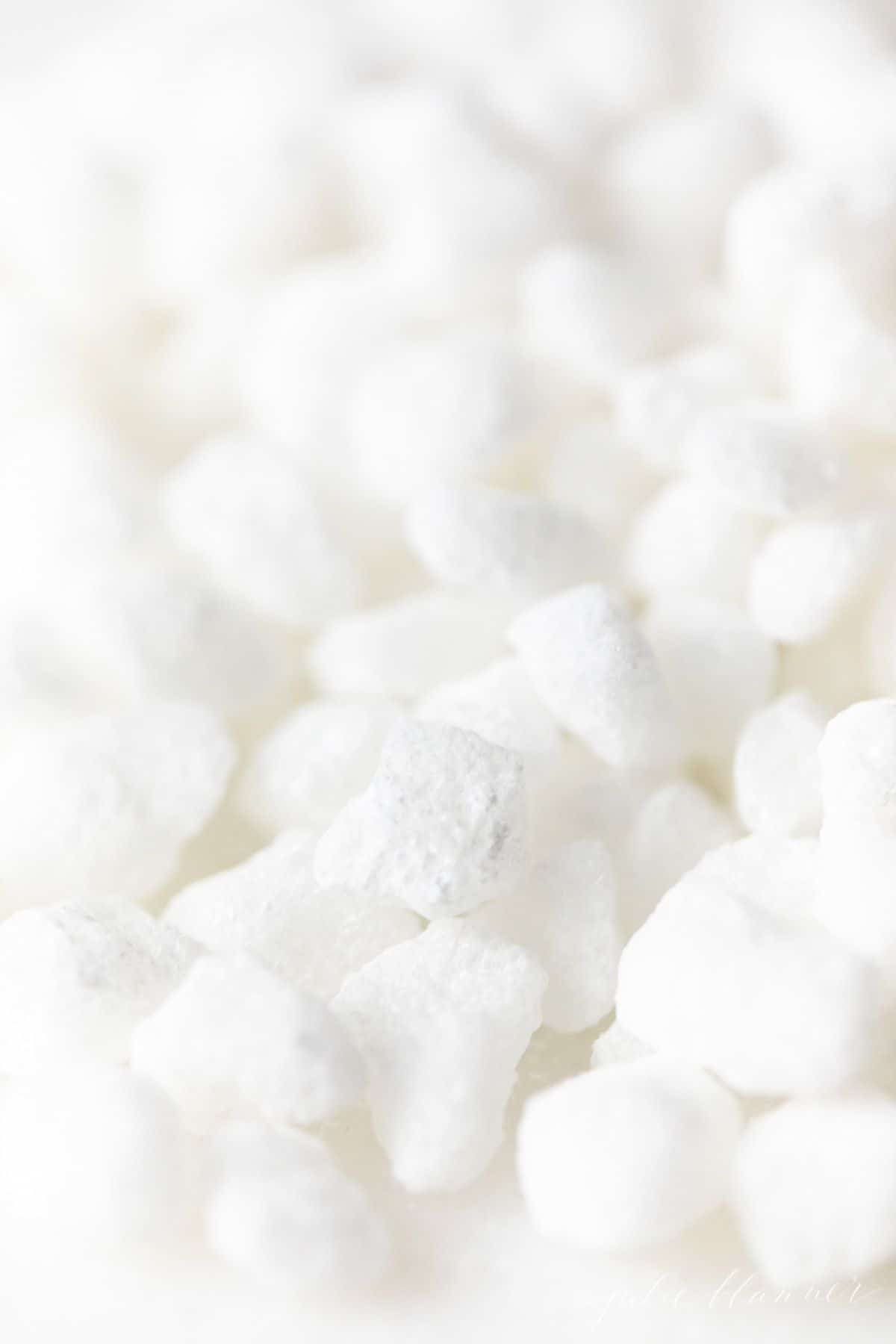 Belgian pearl sugar nibs scattered on a white surface.