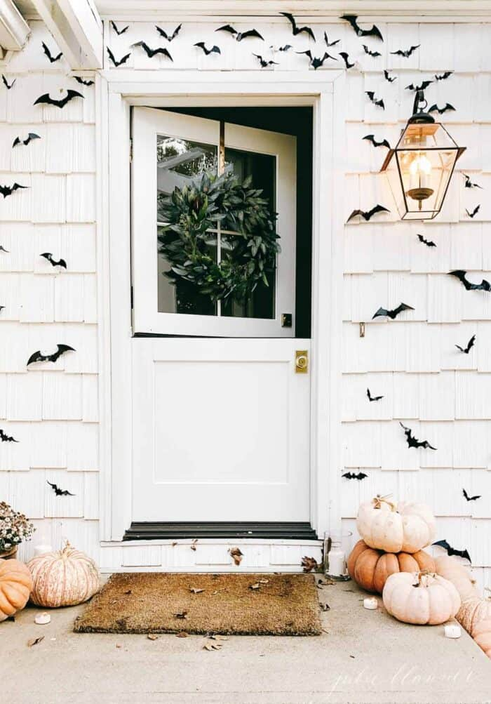A white dutch door on a white cottage home, pumpkins and paper bats surrounding for halloween decor.