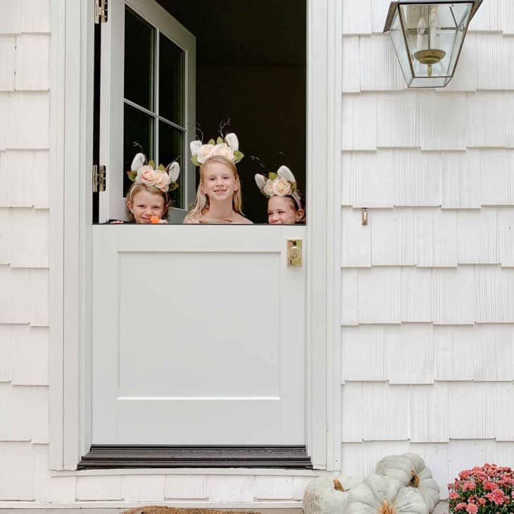 A white cottage with a white dutch door, three little girls peeking over the top.