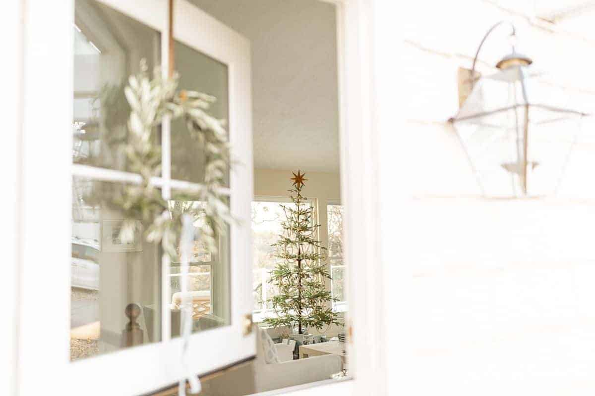 A white exterior dutch door, open looking into a living room with a christmas tree.
