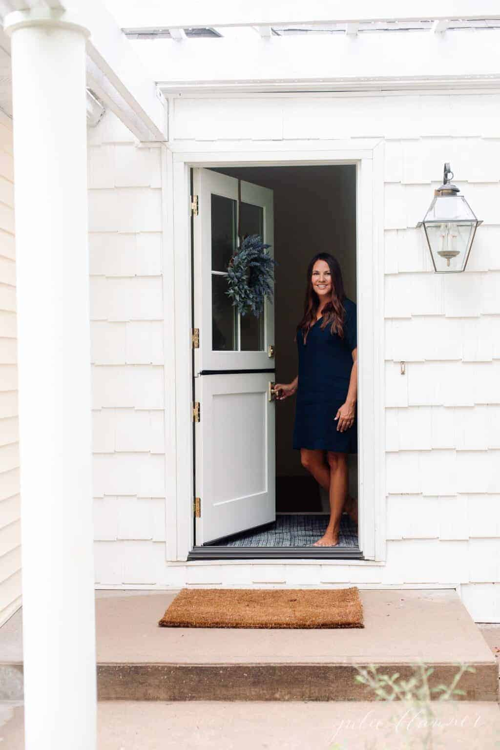A white cottage with a pretty white dutch door, a woman in a navy dress standing at entry with door open.