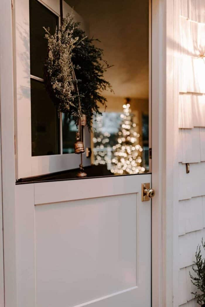 A white exterior dutch door, open at night, looking into a living room with a christmas tree.