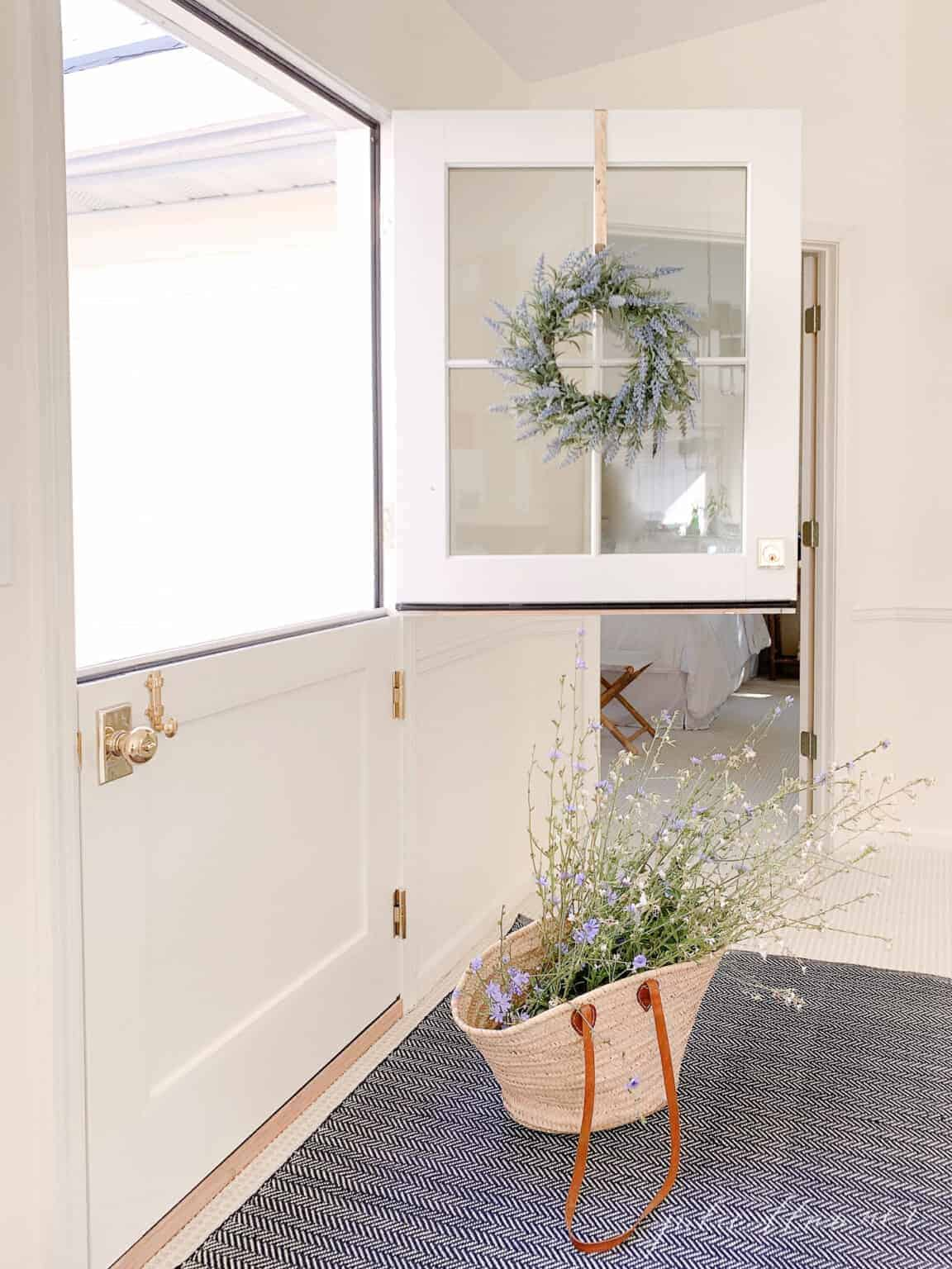 A white living room with large windows and a dutch door with the top half open.