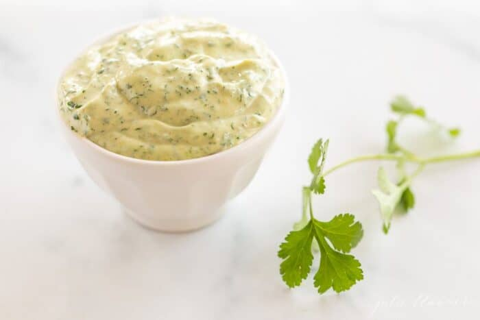 A white bowl full of cilantro lime aioli with a piece of fresh cilantro on a marble surface.