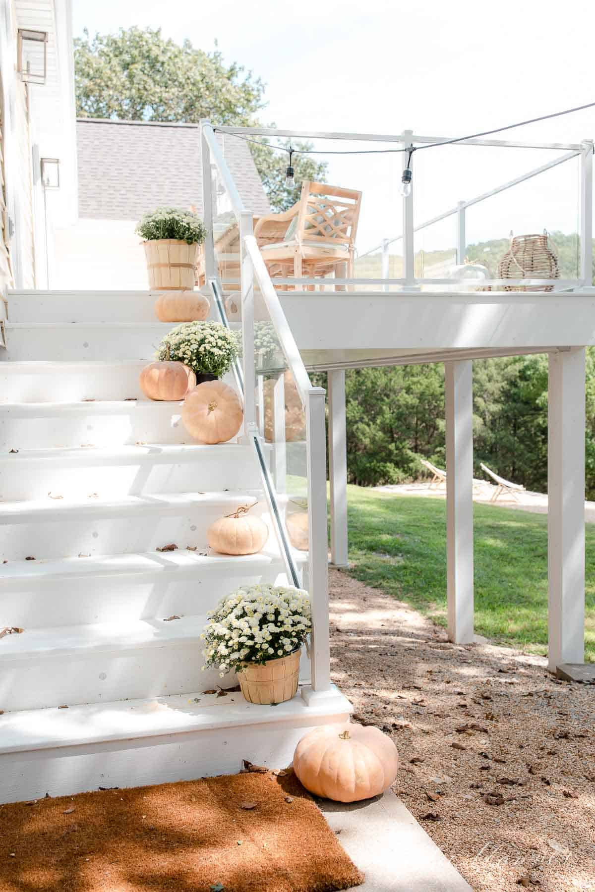 white deck with glass deck railing pumpkins mums and string lights