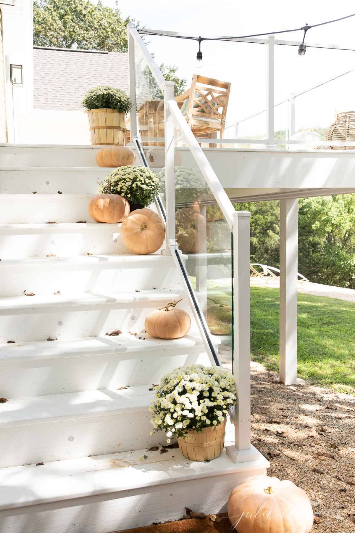 white deck with glass deck railings lined with pumpkins and outdoor lights