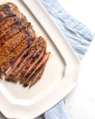 carne asada sliced on a platter with blue napkin