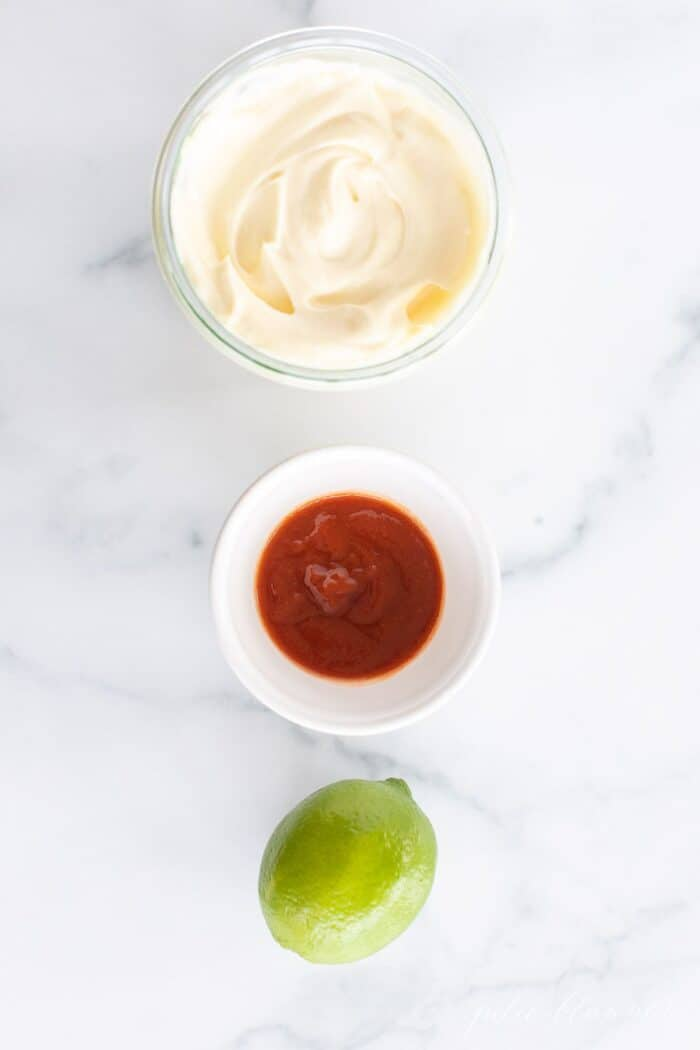 A bowl of mayonnaise, a bowl of sriracha and a whole lime, sitting in a row on a marble surface.