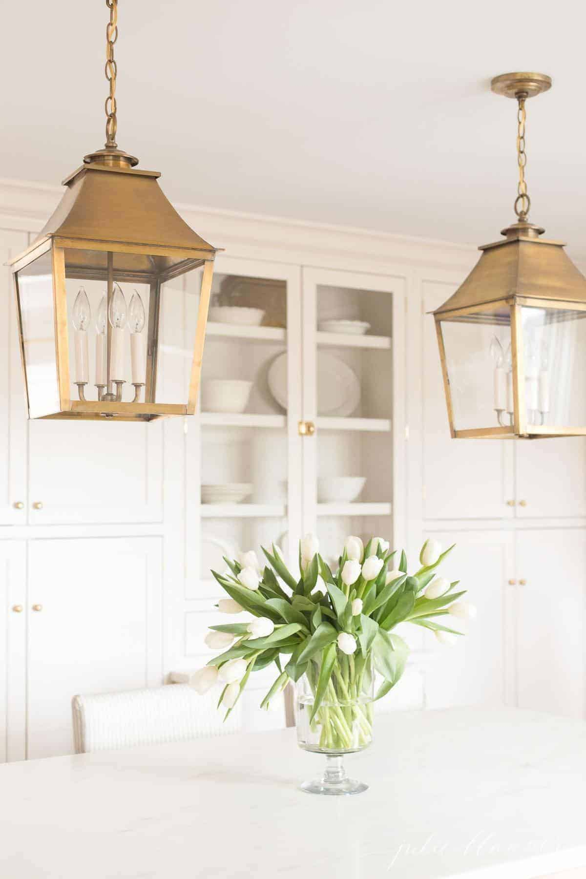 Inset cabinets in a cream kitchen with brass lanterns and a vase of flowers on the island.