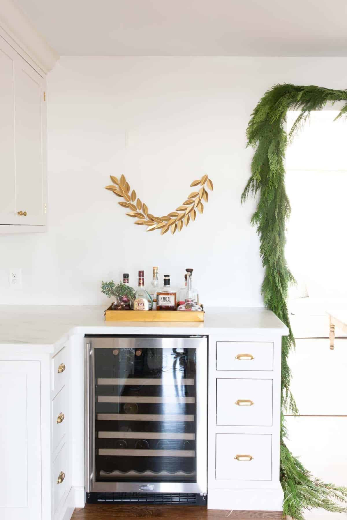 A kitchen with inset cabinets and a wine fridge, Christmas greenery hanging.