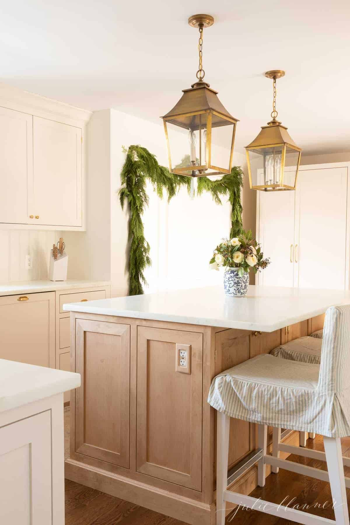 A soft wood island in a cream kitchen decorated with Christmas greenery.