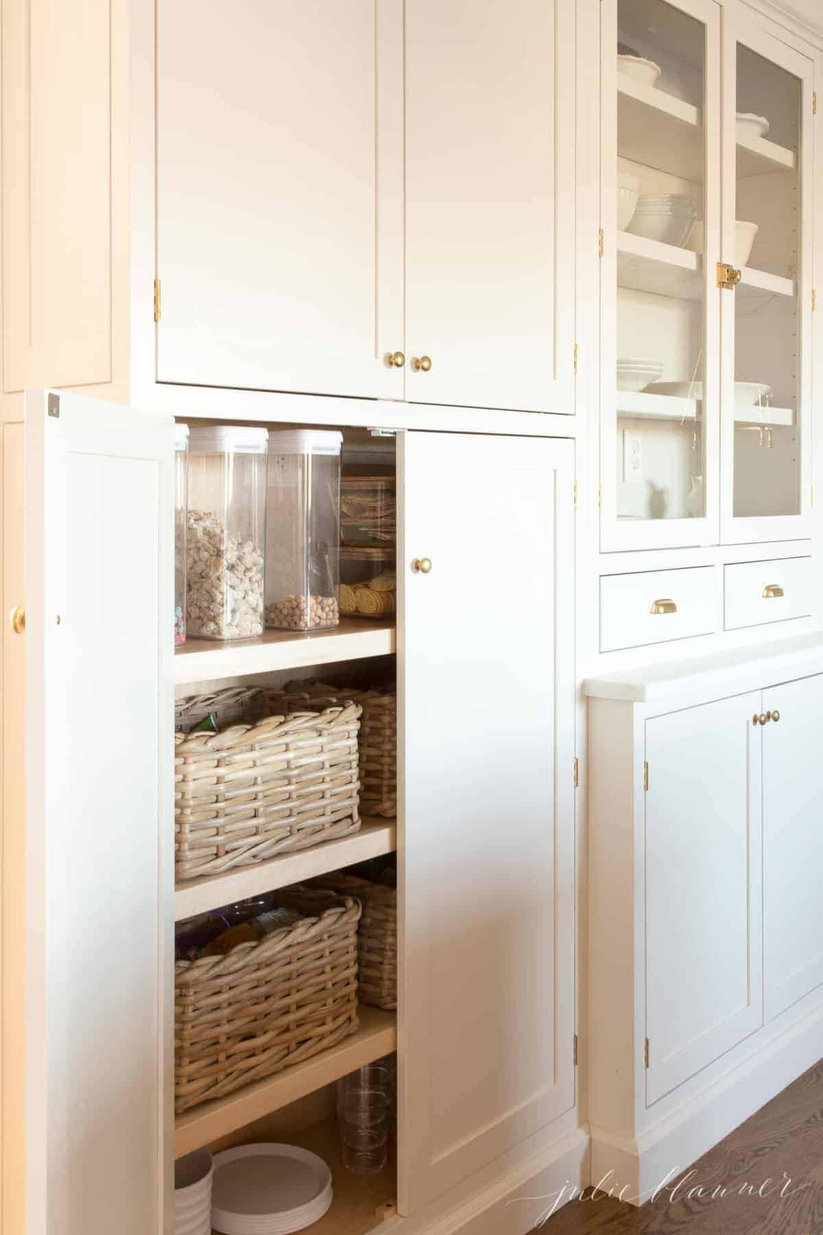 Inset kitchen cabinets with the doors open and pantry goods inside.