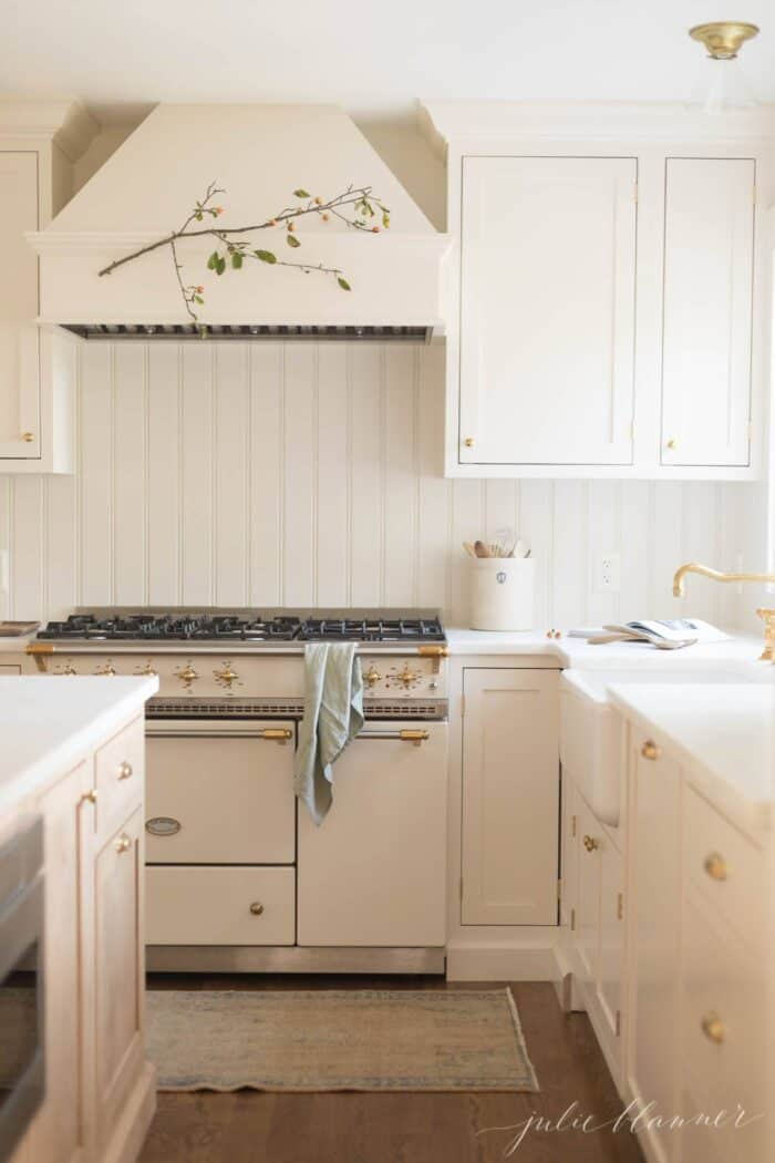A cream classic kitchen with a french range and inset cabinets.