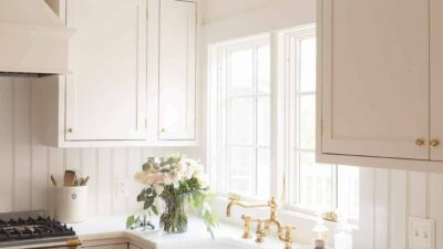 Cream inset cabinets in a kitchen with marble counters and a brass faucet.