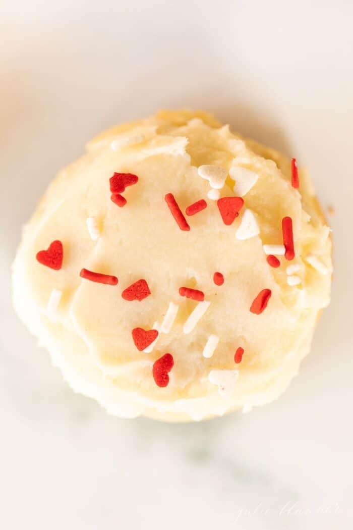 Um único biscoito de açúcar derretido na boca coberto com granulado em uma superfície de mármore.