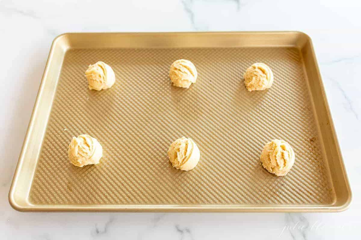 A gold baking sheet topped with melt in your mouth sugar cookies on a marble surface.